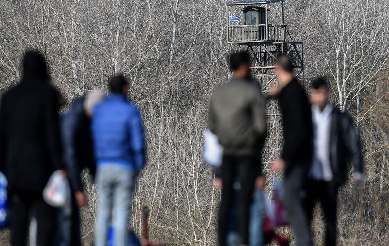 """Migrants look towards to Greek military post guard tower, near the Evros river, near Edirne, in northwestern Turkey, as they waits take a boat to attempt to enter Greece by crossing the river on March 3, 2020. - Turkey's Interior Minister Suleyman Soylu says nearly 50,000 migrants have left Turkey for Europe via the northwestern province of Edirne, bordering Greece. Greece goes onto a state of """"maximum"""" alert to protect its borders and was suspending asylum applications by those who entered the country illegally. (Photo by Ozan KOSE / AFP)"""