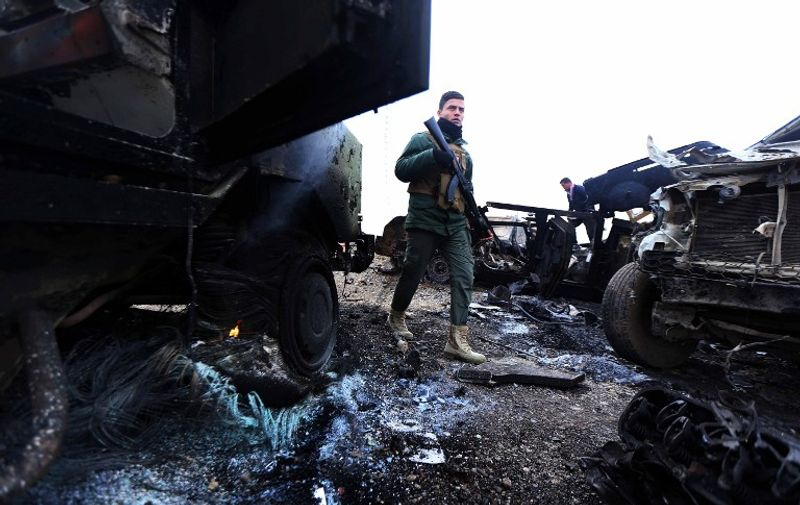 A Peshmerga fighter walks between burning vehicles following a suicide attack carried out by the Islamic State group in Kesarej village, south of to Zummar city, in the northern Iraqi Governorate of Nineveh, near the border with Syria on December 18, 2014. Kurdish forces backed up by US-led warplanes have recaptured a large area in Iraq near the Syrian border in an offensive this week against Islamic State jihadists, a US commander said. AFP PHOTO / SAFIN HAMED / AFP / SAFIN HAMED