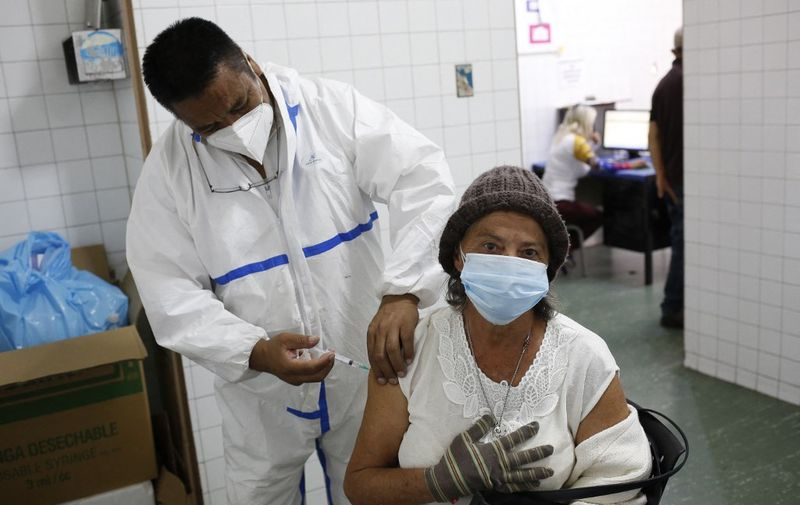 A health worker administers a dose of the Sputnik V vaccine against COVID-19 to an eldery woman at the Victorino Santaella Hospital in Los Teques, Venezuela on April 9, 2021, amid the ongoing coronavirus pandemic. - Like the rest of South America, Venezuela is battling a harsh new pandemic wave fueled, authorities say, by more infectious virus variants from Brazil. (Photo by Pedro Rances Mattey / AFP)