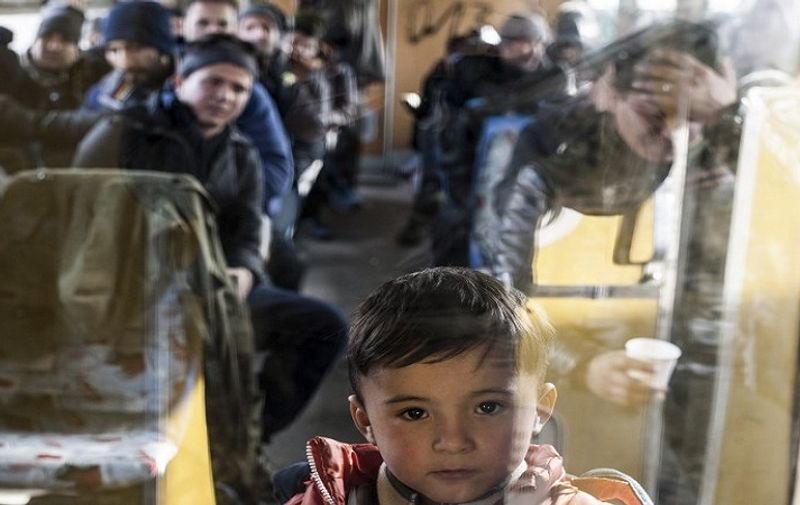A boy is pictured as he waits with other migrants and refugees in a train after crossing the Macedonian border into Serbia, in the town of Presevo  on January 25, 2016.  More than 1 million people from countries like Syria, Iraq or Afghanistan entered Europe last year in what has been called the biggest migration to the continent since World War II.  / AFP / ARMEND NIMANI