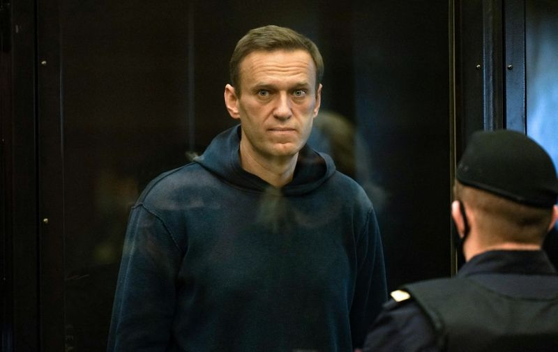 """(FILES) In this file photo taken on February 02, 2021 Russian opposition leader Alexei Navalny, charged with violating the terms of a 2014 suspended sentence for embezzlement, stands inside a glass cell during a court hearing in Moscow. - EU foreign ministers will discuss the case of Alexei Navalny when they hold talks on April 19, 2021, Germany said, as fears grew of the hunger-striking Kremlin critic's deteriorating health while he is being held in a Russian penal colony. (Photo by Handout / Moscow City Court press service / AFP) / RESTRICTED TO EDITORIAL USE - MANDATORY CREDIT """"AFP PHOTO / Moscow City Court press service / handout"""" - NO MARKETING - NO ADVERTISING CAMPAIGNS - DISTRIBUTED AS A SERVICE TO CLIENTS"""