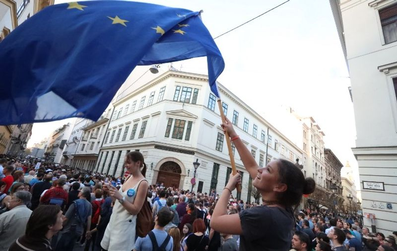 """A young woman waves the European flag as she demonstrates in front of the Central European University (CEU) in Budapest on April 2, 2017, following allegations of the Hungarian Prime Minister that the prestigious university was cheating students by breaking rules. The Central European University (CEU), set up in 1991 after the end of communism and part-funded by Hungarian-US investor George Soros, said in a statement that it """"utterly rejects"""" Hungarian Prime Minister Viktor Orban's allegations. / AFP PHOTO /"""