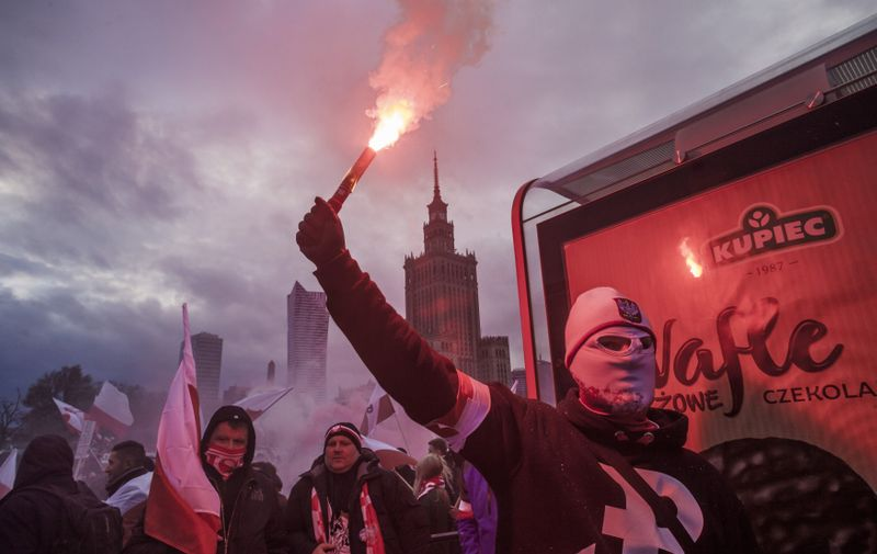 November 11, 2017 - Mazovia, Poland - Member of a far right group holds a flare in the streets of Warsaw celebrating the Independence Day of Poland.  On Saturday, 11 November 2017, in Warsaw, Poland., Image: 355151365, License: Rights-managed, Restrictions: * France Rights OUT *, Model Release: no, Credit line: Profimedia, Zuma Press - News