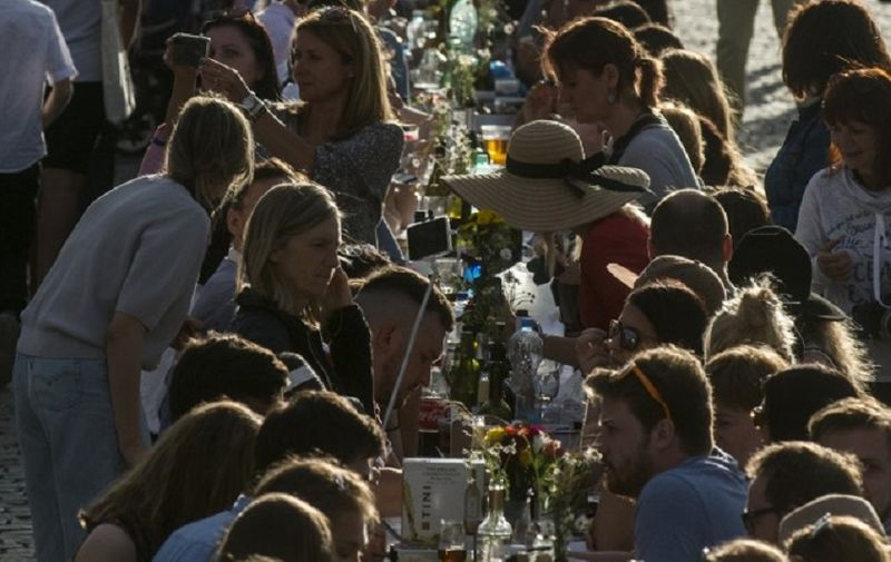 People walk past and sit at a half-kilometre long table set up on the Charles Bridge in Prague to celebrate the end of the restrictions linked to the new coronavirus pandemic on June 30, 2020. - Some 2,000 seats are proposed with people being invited to bring and share food. (Photo by Michal Cizek / AFP)