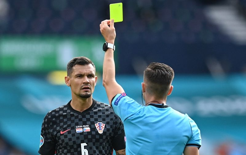 Spanish referee Carlos Del Cerro Grande (R) presents a yellow card to Croatia's defender Dejan Lovren during the UEFA EURO 2020 Group D football match between Croatia and Czech Republic at Hampden Park in Glasgow on June 18, 2021. (Photo by Paul ELLIS / POOL / AFP)