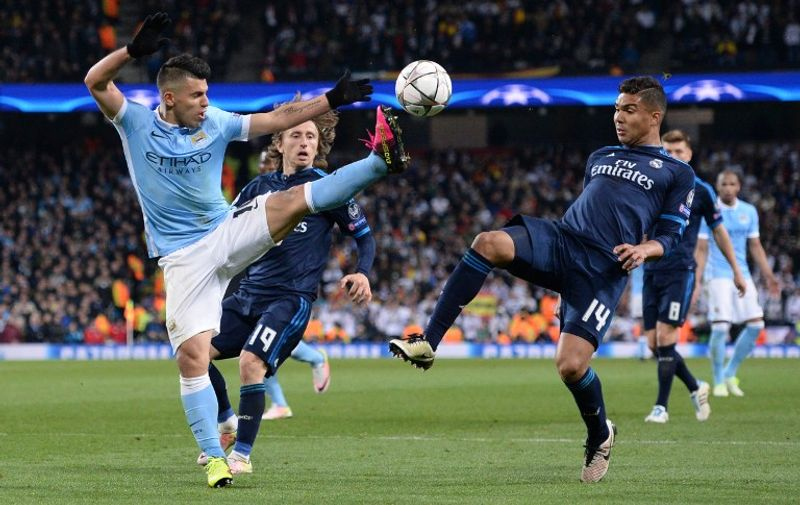 Manchester City's Argentinian striker Sergio Aguero (L) battles with Real Madrid's Croatian midfielder Luka Modric (C) and Real Madrid's Brazilian midfielder Casemiro (R) during the UEFA Champions League semi-final first leg football match between Manchester City and Real Madrid at the Etihad Stadium in Manchester, northwest England, on April 26, 2016. / AFP PHOTO / OLI SCARFF