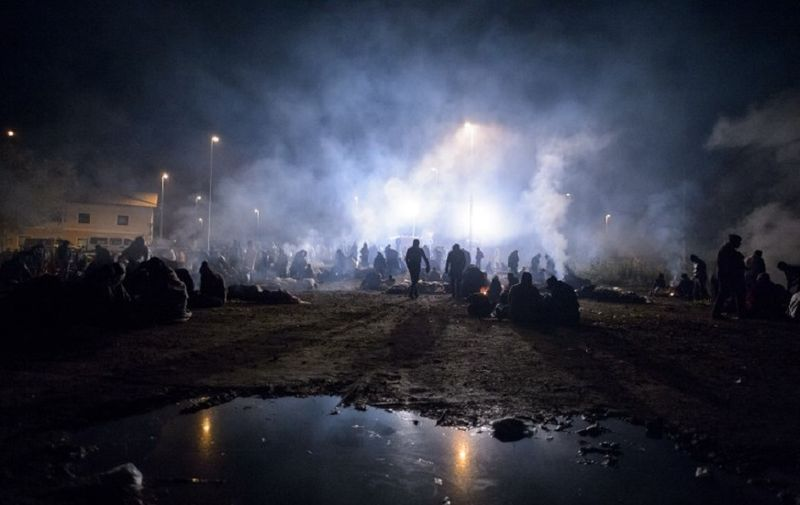 Migrants and refugees arriving from Croatia, waits for buses on the Slovenia-Croatia border on October 22, 2015 in Zavrc. More than 12,600 migrants arrived in Slovenia over a 24-hour period, police said, a record that surpasses even that in Hungary at the height of the crisis in September. More than 600,000 migrants and refugees, mainly fleeing violence in Syria, Iraq and Afghanistan, have braved the dangerous journey to Europe so far this year, the UN said. AFP PHOTO / RENE GOMOLJ (Photo by Rene Gomolj / AFP)