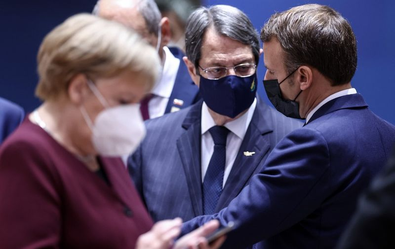 (fromR) France's President Emmanuel Macron, Cyprus' President of the Republic Nicos Anastasiades and Germany's Chancellor Angela Merkel, wearing face masks, attend a face-to-face meeting on the second day of a two days EU summit, in Brussels, on October 16, 2020. (Photo by KENZO TRIBOUILLARD / POOL / AFP)
