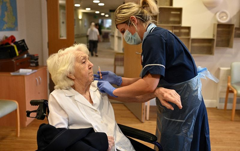 "Practice Nurse Victoria Parkinson gives a dose of the Oxford-AstraZeneca Covid-19 vaccine to resident Ann Wilkinson, 94, at the Belong Wigan care home in Wigan, northwest England, on January 21, 2021. - Some British hospitals resemble a ""war zone"" due to the influx of coronavirus patients in the country's latest wave of the disease, the government's chief scientific adviser said Wednesday. (Photo by Oli SCARFF / AFP)"
