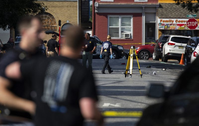 Police officers inspect the crime scene at the Roebling Market on June 17, 2018, the morning after a shooting at an all-night art festival injured 20 people and left one suspect dead in Trenton, New Jersey. (Photo by DOMINICK REUTER / AFP)