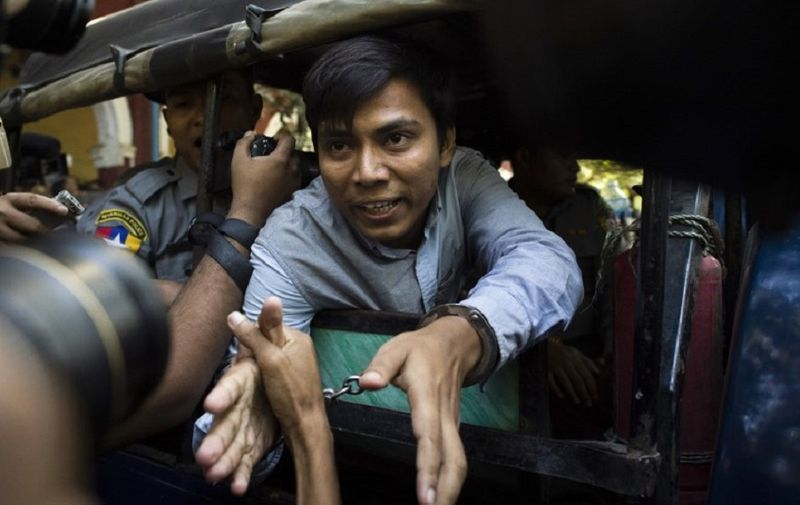 Reuters journalist Kyaw Soe Oo (C) talks to the media as he leaves after a court appearance in Yangon on January 10, 2018. Myanmar police formally filed charges on January 10 against two Reuters reporters accused of breaching the Official Secrets Act, a judge said, an offence that carries up to 14 years in prison. / AFP PHOTO / YE AUNG THU