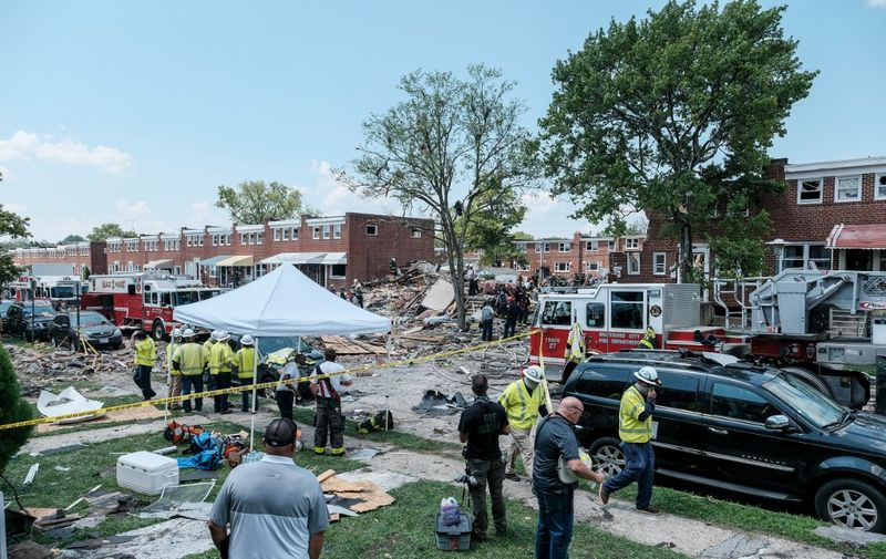BALTIMORE, MD - AUGUST 10: First responders search for survivors at the scene of an explosion on August 10, 2020 in Baltimore, Maryland. Early reports indicate that a gas leak may have caused the massive explosion that leveled three homes, causing multiple injuries and at least one fatality.   Michael A. McCoy/Getty Images/AFP