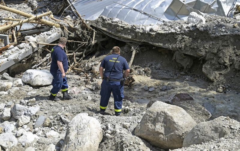 Rescue workers stand amongst rubble at the devastated bobsleigh and luge track at Koenigssee in Schoenau at Koenigssee, southern Germany, on July 19, 2021, after heavy rain hit parts of the country causing flooding. - Koenigssee is the first artificially refrigerated sliding track in the world and hosts World Cup and world championship events. (Photo by UWE LEIN / AFP)