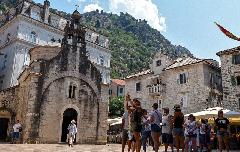 """Tourists stand in front of a church as they visit the medieval city of Kotor on August 21, 2018. - Montenegro's medieval walled city of Kotor, an Adriatic seaport cradled in a spectacular fjord-like bay, has survived centuries of weather and warfare. Now it is facing a different kind of assault, that of gargantuan cruise ships disgorging throngs of tourists threatening a place that was only a few years ago commonly described as a """"hidden gem"""". (Photo by Savo PRELEVIC / AFP)"""