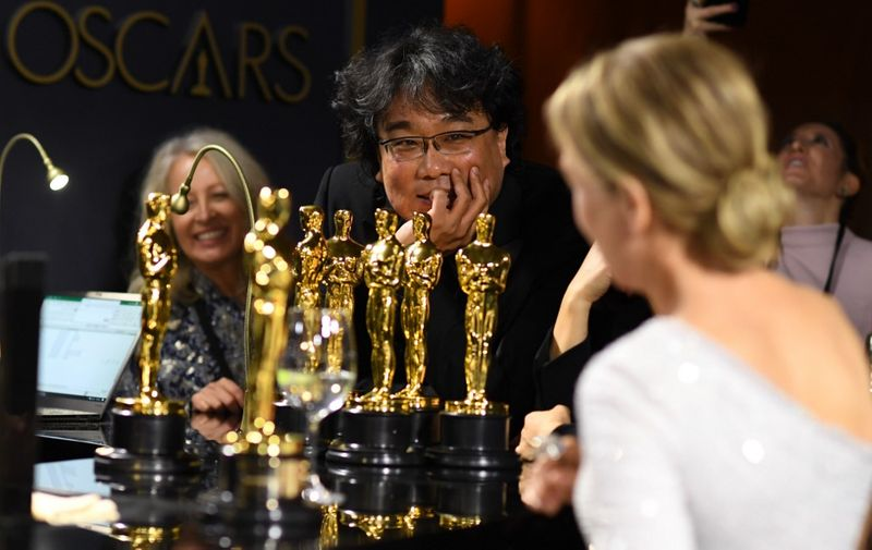 South Korean film director Bong Joon Ho (L) and US actress Renee Zellweger (R) wait for their awards to be engraved as they attend the 92nd Oscars Governors Ball at the Hollywood & Highland Center in Hollywood, California on February 9, 2020. (Photo by VALERIE MACON / AFP)