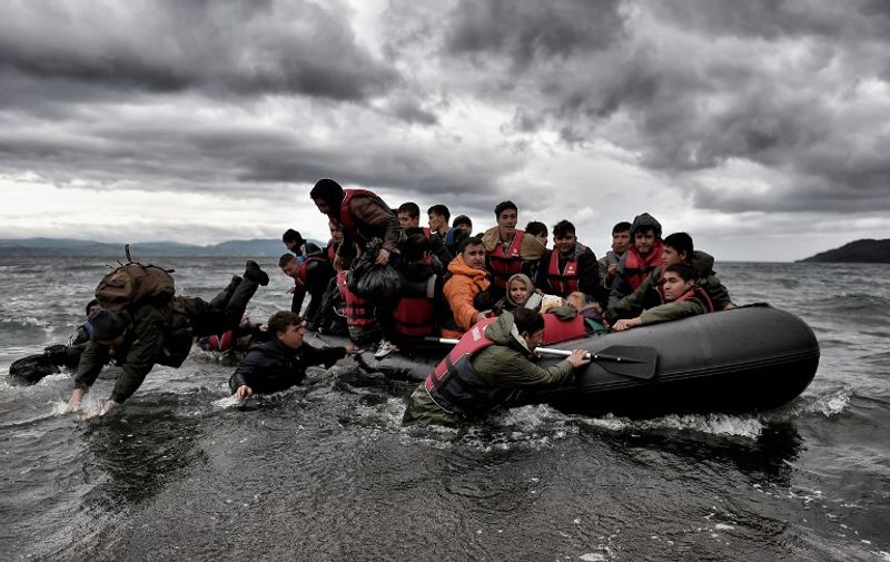 Migrants dive into the sea to help other refugees and migrants to land on the Greek island of Lesbos, on October 24, 2015, after crossing the Aegean sea from Turkey. Bulgaria, Romania and Serbia on October 24 threatened to close their borders if EU countries stopped accepting migrants, as European leaders prepared for a mini summit on the continent's worst refugee crisis since World War II. AFP PHOTO / ARIS MESSINIS