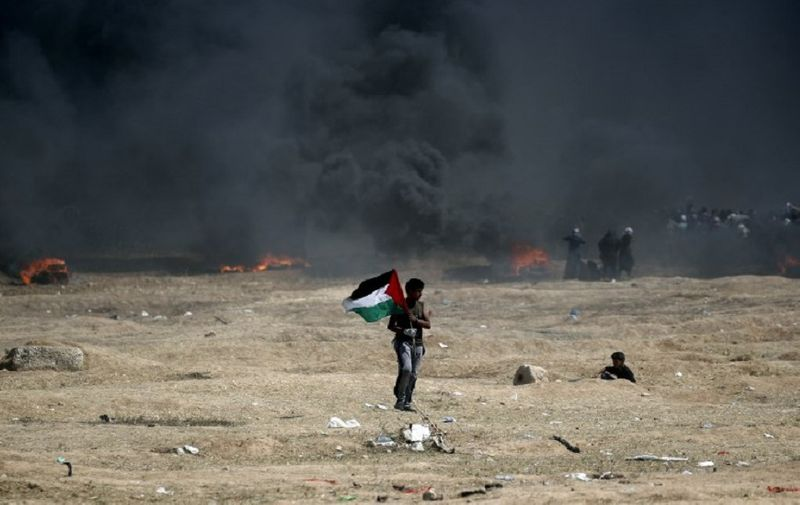 A man holds a Palestinian flag during clashes with Israeli forces near the border between the Gaza strip and Israel, east of Gaza City on May 14, 2018, following the the controversial move to Jerusalem of the United States embassy.  Fifty-two Palestinians were killed by Israeli fire during violent clashes on the Gaza-Israel border coinciding with the opening of the US embassy in Jerusalem, the health ministry in the strip announced.  / AFP PHOTO / THOMAS COEX