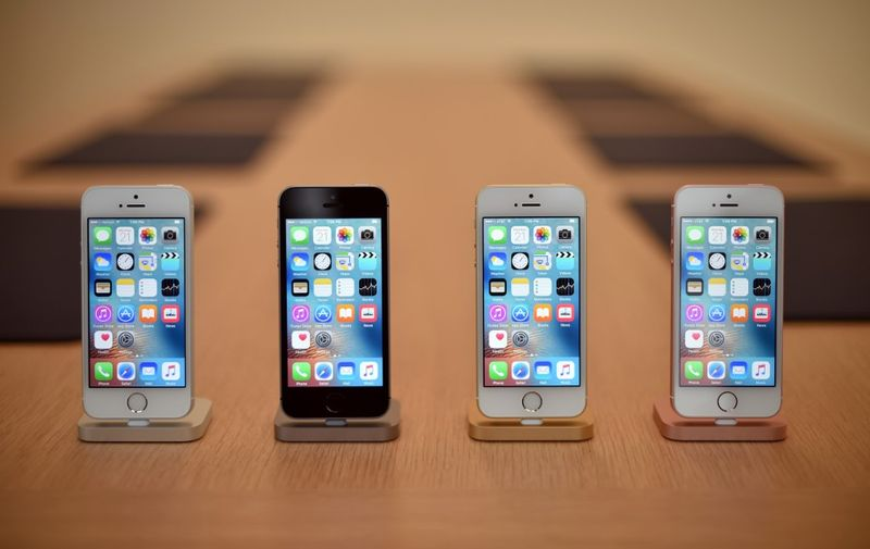 A set of iPhone SE handsets are seen on display during a media event at Apple headquarters in Cupertino, California on March 21, 2016. - The new iPhone SE will debut at $399 for US customers without a contract subsidy, a significant cut from the price of its larger iPhones. (Photo by Josh Edelson / AFP)