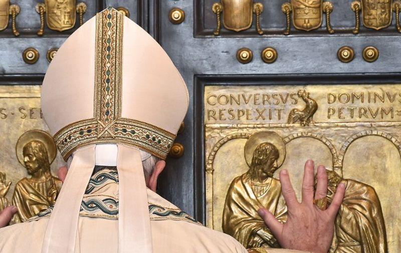 """Pope Francis opens a """"Holy Door"""" at St Peter's basilica to mark the start of the Jubilee Year of Mercy, on December 8, 2015 in Vatican. In Catholic tradition, the opening of """"Holy Doors"""" in Rome symbolises an invitation from the Church to believers to enter into a renewed relationship with God.   AFP PHOTO / VINCENZO PINTO / AFP / VINCENZO PINTO"""