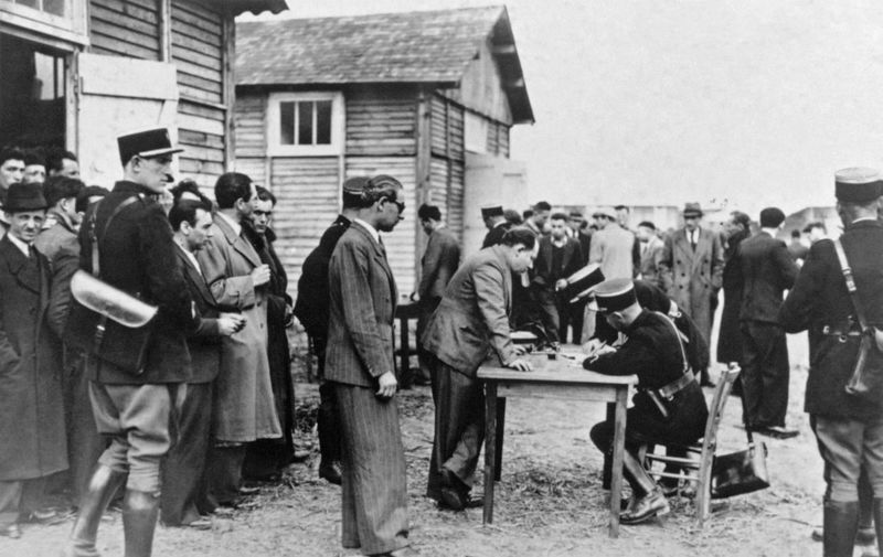 Picture taken on May 1941 at Pithiviers showing foreign Jews who get registered by French policemen after their arrival in the transit camp. These registration was the beginning of the deportation process towards the extermination camps in Germany and in East Europe. (Photo by - / AFP)
