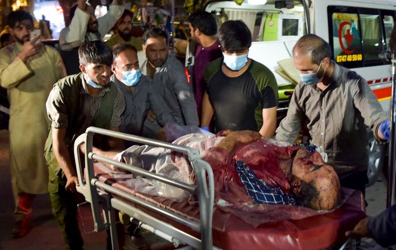 EDITORS NOTE: Graphic content / Volunteers and medical staff bring an injured man for treatment after two powerful explosions, which killed at least six people, outside the airport in Kabul on August 26, 2021. (Photo by Wakil KOHSAR / AFP)