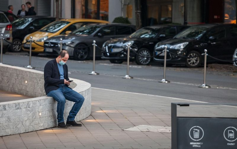 BELGRADE, SERBIA - OCTOBER 10, 2020: Man wearing a respiratory face mask checking apps on his smartphone in the street of Belgrade, during the coronavirus covid 19 health crisis.  Picture of a white caucasian young male in belgrade, serbia, sitting and checking her smartphone in the streets of Belgrade, capital city of Serbia, while wearing a respiratory face mask during the coronavirus health crisis.,Image: 566911241, License: Royalty-free, Restrictions: , Model Release: no