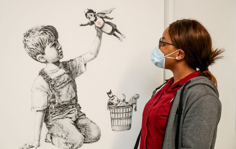 "(FILES) A handout picture received from University Hospital Southampton on May 7, 2020 shows a member of staff posing with an artwork by street artist Banksy called ""Game Changer"", showing a boy playing with a nurse superhero toy with figures of Batman and Spiderman discarded in a basket as a tribute to NHS staff who are continuing to work during the COVID-19 pandemic, on a wall at the University Hospital Southampton, southern England. - painting by the British street artist Banksy sold for a record £16.75 million ($23.1 million, 19.4 million euros) on March 23, 2021, with proceeds going to the state-run health service. The painting, ""Game Changer"", sold for £14.4 million plus costs -- the highest ever for a Banksy painting -- after fierce competition between bidders in a nail-biting sale at Christie's auction house in London. (Photo by Stuart MARTIN / UNIVERSITY HOSPITAL SOUTHAMPTON / AFP) / RESTRICTED TO EDITORIAL USE - MANDATORY CREDIT ""AFP PHOTO / UNIVERSITY HOSPITAL SOUTHAMPTON / STUART MARTIN "" - NO MARKETING - NO ADVERTISING CAMPAIGNS - MANDATORY MENTION OF ARTIST UPON PUBLICATION - DISTRIBUTED AS A SERVICE TO CLIENTS"