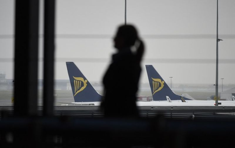 A groundstaff stands in a terminal with Ryanair planes in background during what could be the biggest strike in the airline's history, at Charleroi Airport in Gosselies on September 28 2018. - Ryanair cancelled scores of European flights on September 28, 2018 as unions staged what they warned could be the biggest strike in the airline's history. The Dublin-based carrier has played down fears of widespread disruption but confirmed it would cancel nearly 250 flights. (Photo by JOHN THYS / AFP)