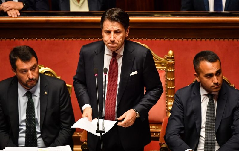 """Italian Prime Minister Giuseppe Conte (C), flanked by Deputy Prime Minister and Interior Minister Matteo Salvini (L) and by Deputy Prime Minister and Minister of Economic Development, Labour and Social Policies, Luigi Di Maio (R), reacts as he delivers a speech at the Italian Senate, in Rome, on August 20, 2019, as the country faces a political crisis. - Italy's Premier Conte says to offer resignation during his speech at the Senate after calling Italy's far-right Interior Minister Matteo Salvini """"irresponsible"""" to spark a political crisis by pulling the plug on the governing coalition. (Photo by Andreas SOLARO / AFP)"""