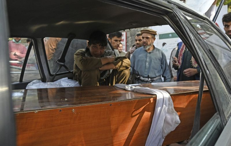 A relative mourns inside a car next to the coffin of a victim of the August 26 twin suicide bombs, which killed scores of people including 13 US troops outside Kabul airport, at a hospital run by the Italian NGO Emergency in Kabul on August 27, 2021. (Photo by Aamir QURESHI / AFP)