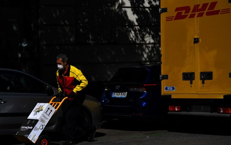 A DHL employee delivers boxes in Madrid on April 2, 2020 amid a national lockdown to fight the spread of the COVID-19 coronavirus. - The coronavirus death toll in Spain surged past 10,000 after a record 950 deaths in 24 hours, with the number of confirmed cases passing the 110,000 mark, the government said. (Photo by GABRIEL BOUYS / AFP)