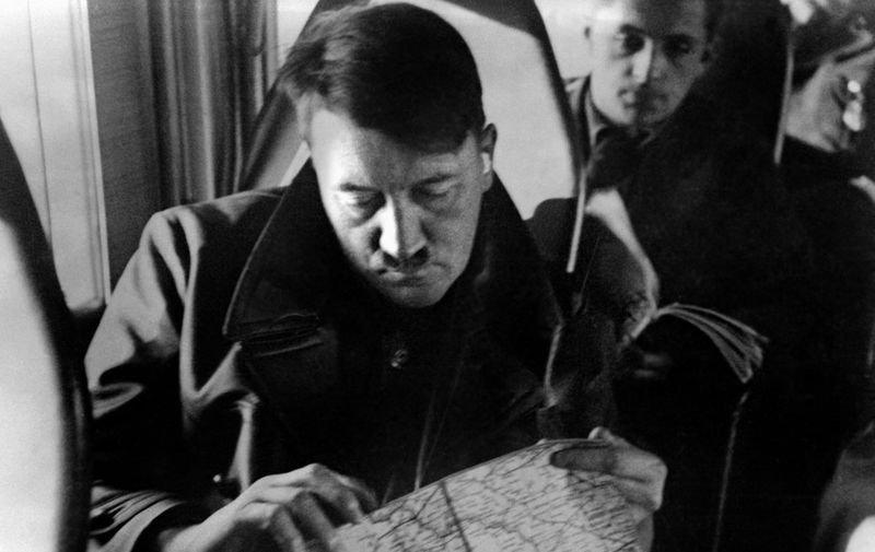 An undated picture shows German Nazi Chancellor Adolf Hitler in a plane looking at a map with Governor-general of Nazi-occupied Poland, Hans Frank in the background. AFP PHOTO / FRANCE PRESSE VOIR (Photo by FRANCE PRESSE VOIR / AFP)