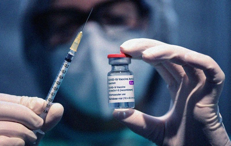 "(FILES) In this file photo taken on March 09, 2021 a medical worker holds a syringe and a vial of the British-Swedish AstraZeneca/Oxford vaccine during a vaccination campaign at the National Museum of Science and Technology Leonardo Da Vinci. - Danish health authorities said on March 11, 2021 they were temporarily suspending the use of AstraZeneca's Covid-19 vaccine as a precaution after some patients developed blood clots since receiving the jab. The move comes ""following reports of serious cases of blood clots among people vaccinated with AstraZeneca's Covid-19 vaccine"", the Danish Health Authority said in a statement. (Photo by Miguel MEDINA / AFP)"