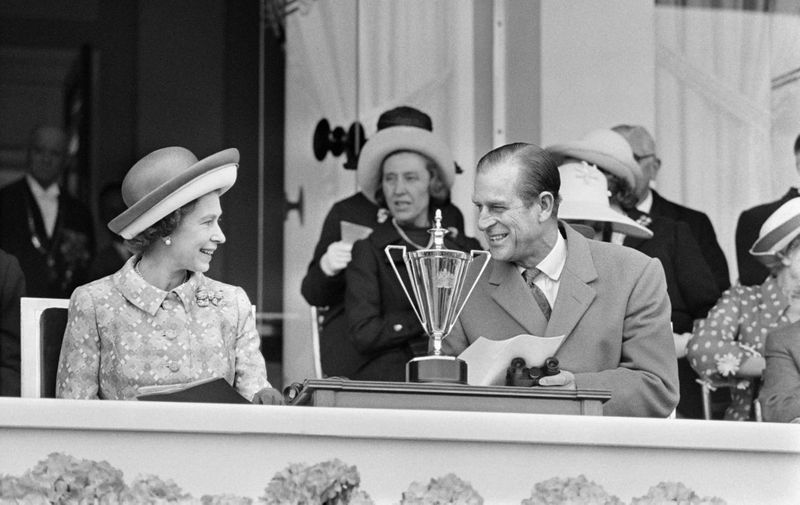 "(FILES) In this file photograph taken on May 18, 1972, Britain's Queen Elizabeth II (L) and her husband Prince Philip Duke of Edinburgh speak as they attend a horse race at Longchamp Racecourse, on the outskirts of Paris during a five-day official visit to France. - French President Emmanuel Macron paid tribute to Prince Philip on April 10, 2021, following his death on April 9, at the age of 99 and sent his condolences to the queen. Philip ""lived an exemplary life defined by bravery, a sense of duty and commitment to youth and the environment"", he said on Twitter. Macron later recalled the prince's closeness to France and his many stays on French soil, from childhood to as recently as 2014, on the 70th anniversary of the D-Day landings. Citing the Duke of Edinburgh's participation in World War II and medals including the Legion d'honneur, Macron said ""he knew the price paid by our two countries, allies and brothers in the fight for freedom."" (Photo by STAFF / AFP)"