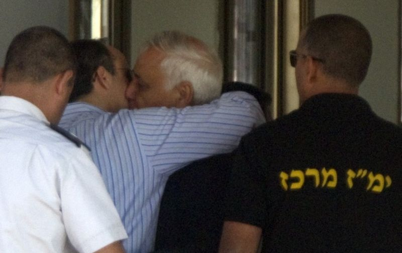 Former Israeli president Moshe Katsav (C) kisses his son as he arrives at the Maasiyahu Prison in Ramla on December 7, 2011. Katsav will begin his seven-year prison sentence after his conviction on two counts of rape, sexual harassment, indecent acts and obstruction of justice. AFP PHOTO/JACK GUEZ / AFP PHOTO / JACK GUEZ