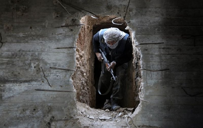 A Syrian rebel fighter from the Failaq al-Rahman brigade comes out of a hiding position on the frontline against regime forces in the town of Arbin in the eastern Ghouta region on the outskirts of the capital Damascus on February 26, 2016.  A partial ceasefire between Syria's regime forces and non-jihadist rebel fighters is due to take effect at midnight (2200 GMT) local time.  / AFP PHOTO / AMER ALMOHIBANY