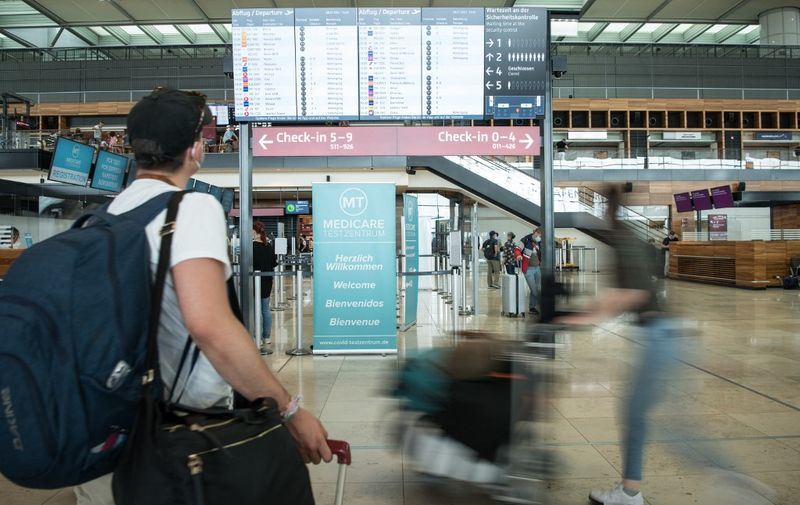 """Passengers with face masks and bags stand and walk in front of a display board for departures at the BER """"Willy Brandt"""" airport in Brandenburg, near Schoenefeld and Berlin, on July 28, 2021. - When the general testing requirement for travelers entering German will start remains undetermined. The plan is to make testing compulsory for all travelers without proof of vaccination nor proof of recovery - regardless of which country they are traveling from and on which means of transport. (Photo by STEFANIE LOOS / AFP)"""