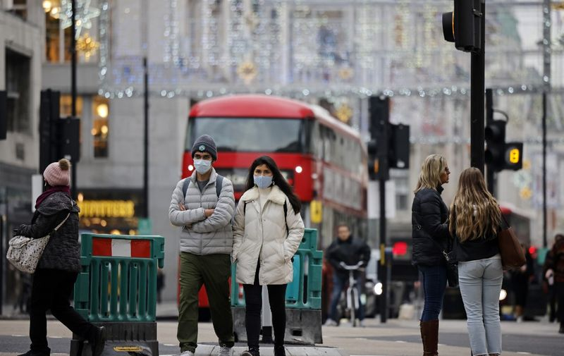 "Pedestrians wearing a protective face coverings to combat the spread of the coronavirus, walk down Oxford Street in central London on November 27, 2020, as life under a second lockdown continues in England. - England will return to a regional tiered system when the national stay-at-home order ends on December 2, and 23.3 million residents in the worst-hit areas are set to enter the ""very high"" alert level. (Photo by Tolga Akmen / AFP)"