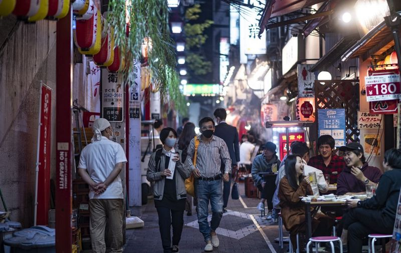 People wearing face masks as a preventive measure against the Covid-19 coronavirus visit the restaurant area of Omoide Yokocho alleyway in Shinjuku district of Tokyo on November 19, 2020. (Photo by Philip FONG / AFP)