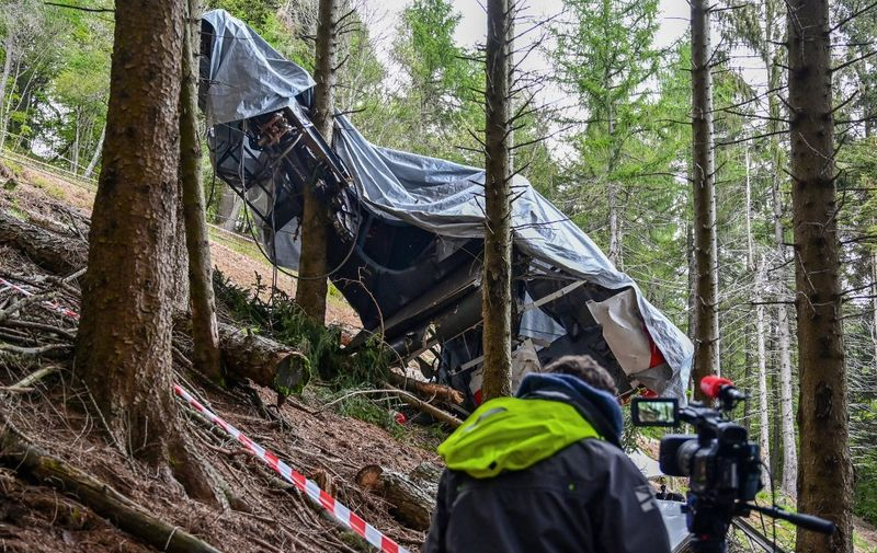A view shows a journalist working by the cabin's wreckage covered with a tarpaulin on May 26, 2021 on the slopes of the Mottarone peak above Stresa, Piedmont, three days after a cable car crash that killed 14. - Investigators probed the causes of a terrifying cable car crash in the Italian mountains that left 14 people dead, including five Israelis, and a young child fighting for life. (Photo by MIGUEL MEDINA / AFP)