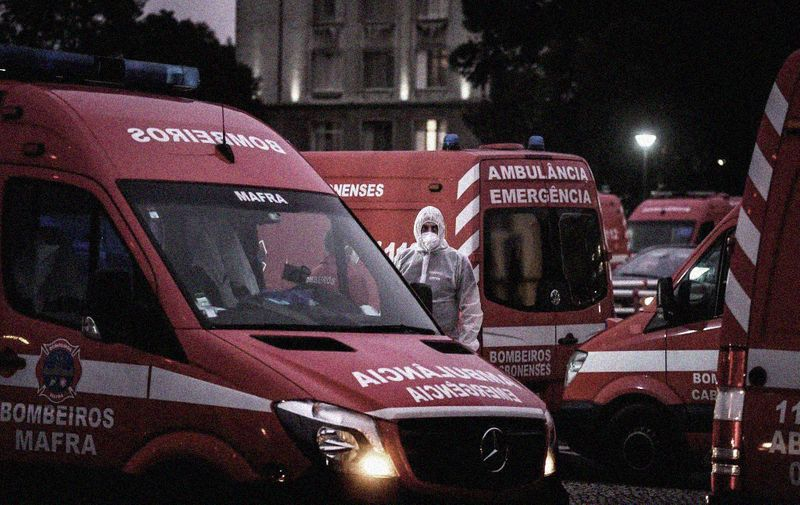 """A health worker wearing a protective suit stands in the middle of dozens of ambulances waiting outside the Covid-19 emergency services of Santa Maria Hospital in Lisbon on January 28, 2021. - Portugal reported twin Covid records with 303 new deaths and 16,432 cases in a 24-hour period, prompting a decision to limit foreign travel to """"special cases"""". (Photo by PATRICIA DE MELO MOREIRA / AFP)"""