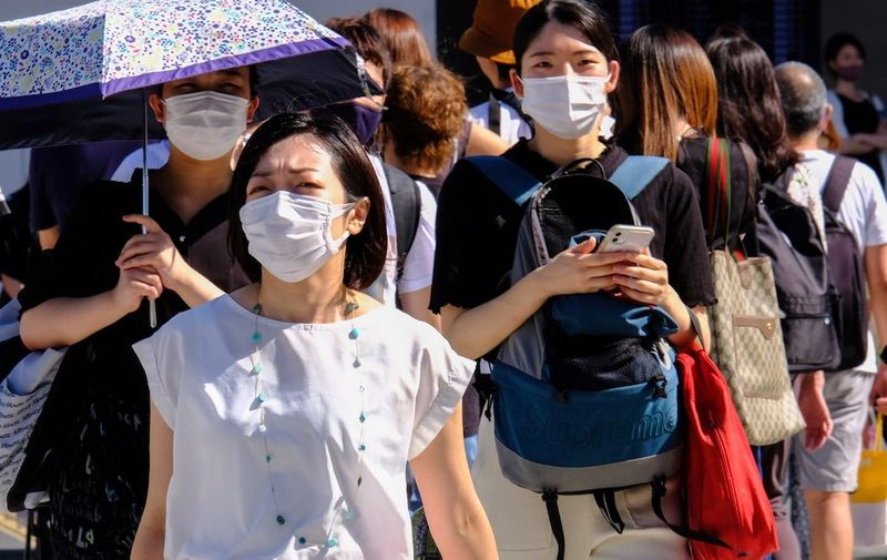 People wearing masks as a preventive measure against the spread of covid-19 cross at Shibuya Crossing in Tokyo. Tokyo reports record 2,848 new coronavirus cases; nationwide tally 7,629. Shibuya Crossing in Tokyo, Japan - 16 July 2021,Image: 623780673, License: Rights-managed, Restrictions: , Model Release: no, Credit line: Profimedia