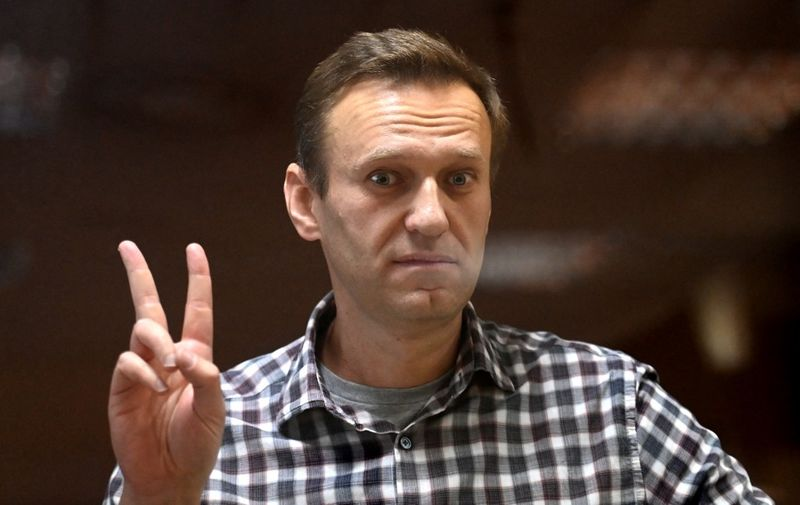 (FILES) In this file photograph taken on February 20, 2021, Russian opposition leader Alexei Navalny gestures as he stands inside a glass cell during a court hearing at the Babushkinsky district court in Moscow. - Russian prison officials are threatening to start force-feeding jailed Kremlin critic Alexei Navalny, his team said on April 12, 2021, after he lost eight kilograms (18 pounds) since starting a hunger strike. (Photo by Kirill KUDRYAVTSEV / AFP)