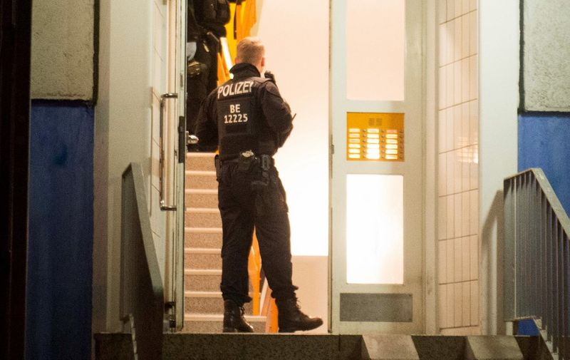 Policemen enter a residential building in Berlin's Marzahn-Hellersdorf district, where they carried out a raid, on January 14, 2020. - German police carried out raids on suspected Islamist militants across the country early Tuesday, January 14, over allegations they were plotting a violent attack, Berlin officials said. German authorities are on high alert for Islamist threats to Europe's most populous country, which has in recent years suffered several attacks. (Photo by Dennis BRAETSCH / DPA / AFP) / Germany OUT
