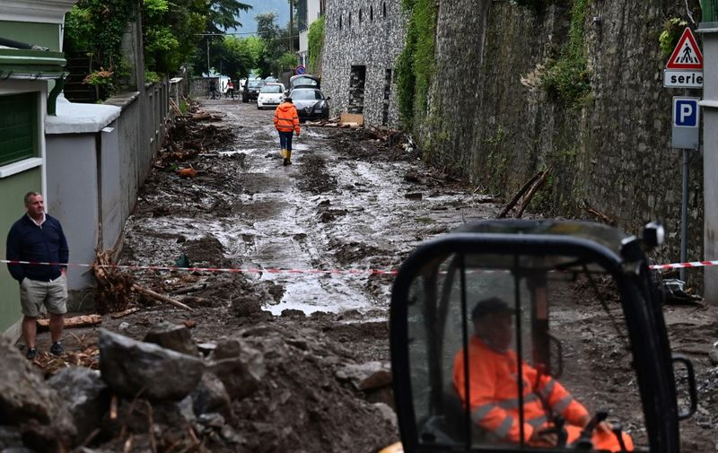 A worker uses an excavator to clear the damages caused by a landslide in Laglio after heavy rain caused floods in towns surrounding Lake Como in northern Italy, on July 28, 2021. (Photo by MIGUEL MEDINA / AFP)
