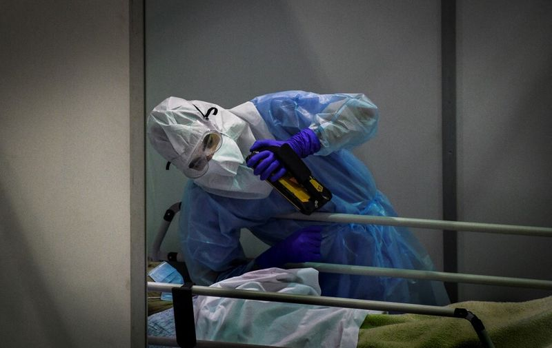 A health worker wearing protective gear holds a tablet to help a patient speak with his family at the Portimao Arena sports pavilion converted in a field hospital for Covid-19 patients at Portimao, in the Algarve region, on February 9, 2021. (Photo by PATRICIA DE MELO MOREIRA / AFP)