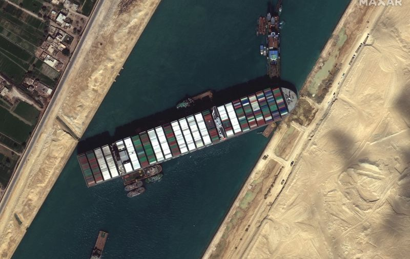 """This satellite imagery released by Maxar Technologies shows tug boats and dredgers on March 27, 2021, attempting to free the Taiwan-owned MV Ever Given lodged sideways and impeding all traffic across Egypt's Suez Canal. - The container ship, which is longer than four football fields, has been wedged diagonally across the entire canal since March 23, shutting the waterway in both directions. The blockage has caused a huge traffic jam for more than 200 ships at either end of the 193-km (120-mile) long canal and major delays in the delivery of oil and other products. (Photo by - / Satellite image ©2021 Maxar Technologies / AFP) / RESTRICTED TO EDITORIAL USE - MANDATORY CREDIT """"AFP PHOTO / Satellite image ©2021 Maxar Technologies"""" - NO MARKETING - NO ADVERTISING CAMPAIGNS - DISTRIBUTED AS A SERVICE TO CLIENTS"""