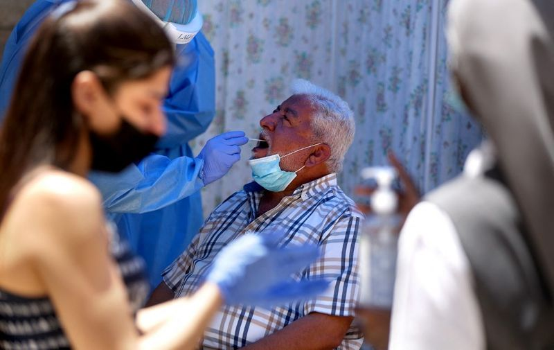 A man is tested for the novel coronavirus by a nurse with the mobile crew of the Lebanese American University Medical Center, at the Order of Malta dispensary, in the southern Lebanese local authority of Roum in the town of Jezzine on May 21, 2020. (Photo by PATRICK BAZ / AFP)