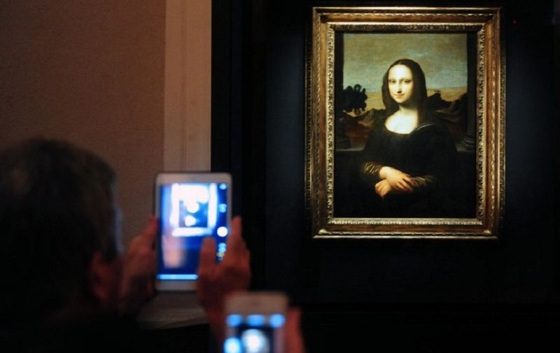 """Members of the media take pictures during the media preview of The World Premiere of Leonardo Da Vinci's painting """"Earlier Mona Lisa"""" exhibition in Singapore on December 15, 2014. The World Premiere of Leonardo Da Vinci's exhibition will begin on December 16 till February 1, 2015. AFP PHOTO / MOHD FYROL RESTRICTED TO EDITORIAL USE, MANDATORY MENTION OF THE ARTIST UPON PUBLICATION, TO ILLUSTRATE THE EVENT AS SPECIFIED IN THE CAPTION."""