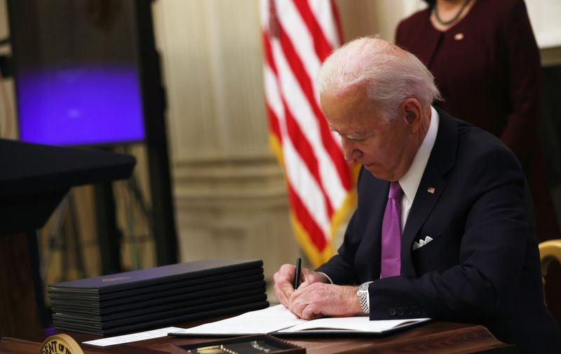 WASHINGTON, DC - JANUARY 21: U.S. President Joe Biden signs an executive order during an event in the State Dining Room of the White House January 21, 2021 in Washington, DC. President Biden delivered remarks on his administration's COVID-19 response, and signed executive orders and other presidential actions.   Alex Wong/Getty Images/AFP